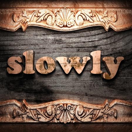 slowly: Golden word on wood