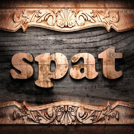 spat: Golden word on wood