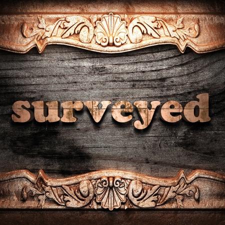 surveyed: Golden word on wood