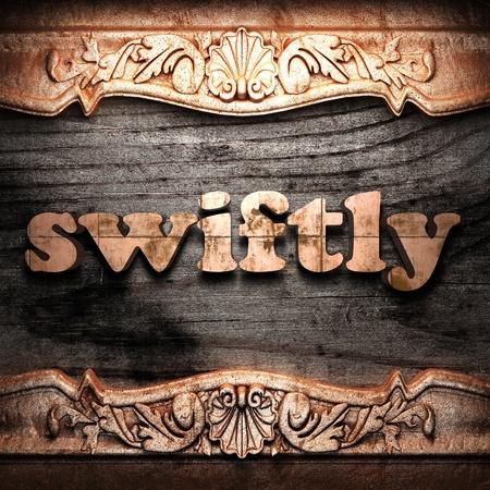 swiftly: Golden word on wood
