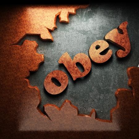 obedecer: palabra de madera sobre hormigón rojo