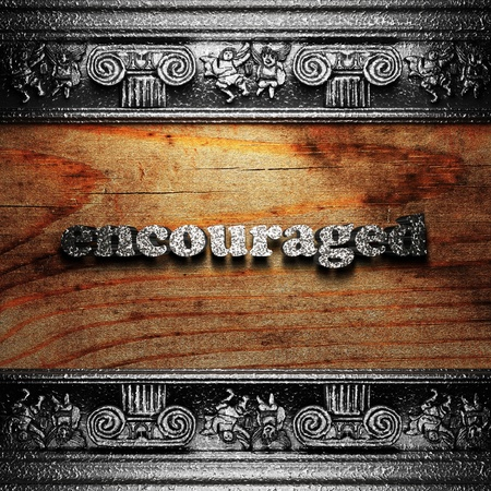 encouraged: iron word on wood made in 3D Stock Photo