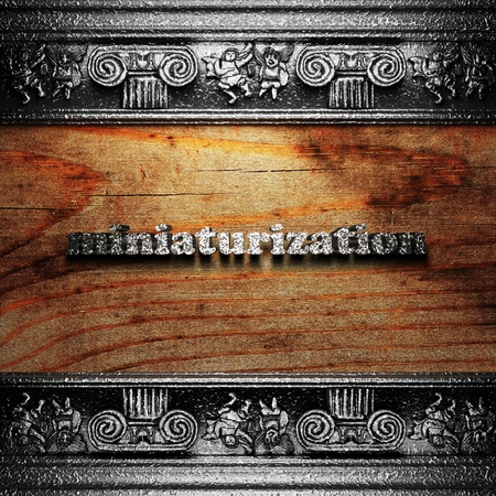 miniaturization: iron word on wood made in 3D Stock Photo