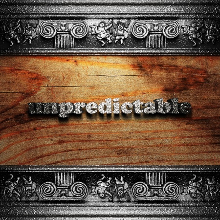 unpredictable: iron word on wood made in 3D Stock Photo