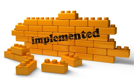 implemented: Word on yellow wall Stock Photo