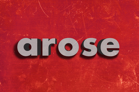 arose: gray word on red wall
