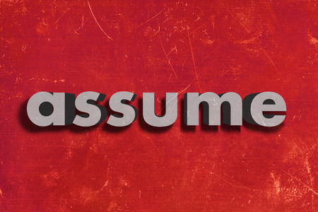 assume: gray word on red wall