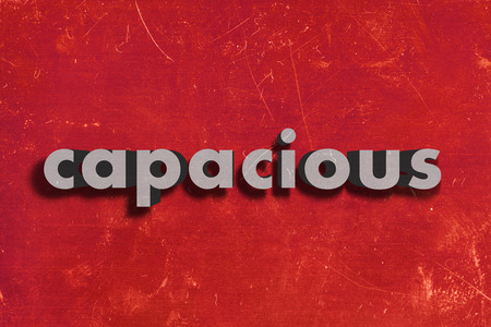 capacious: gray word on red wall