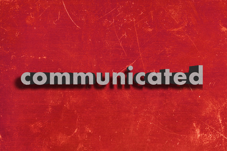 communicated: gray word on red wall