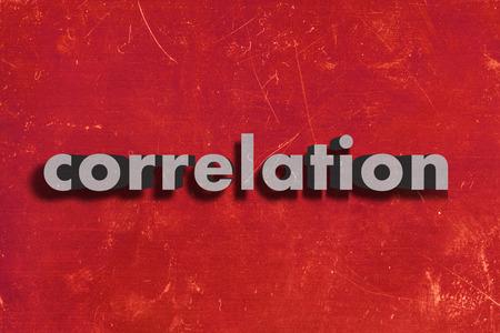 correlation: grigio parola su muro rosso