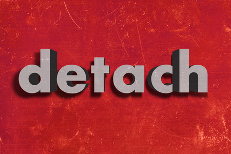 detach: gray word on red wall