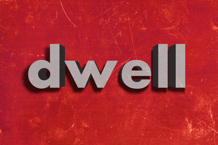 dwell: gray word on red wall