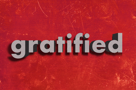gratified: gray word on red wall