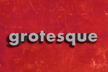 grotesque: gray word on red wall