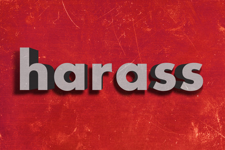harass: gray word on red wall
