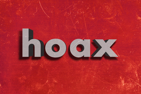 hoax: gray word on red wall