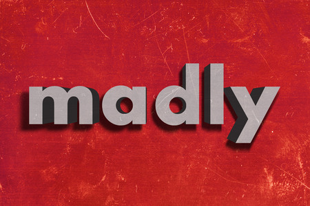 madly: gray word on red wall