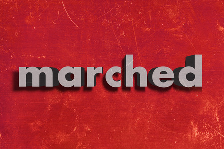 marched: gray word on red wall
