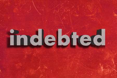 indebted: gray word on red wall