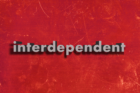 interdependent: gray word on red wall