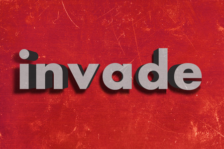 invade: gray word on red wall