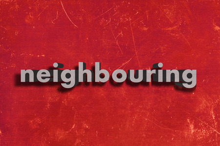 neighbouring: gray word on red wall
