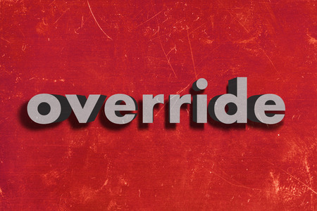 override: gray word on red wall