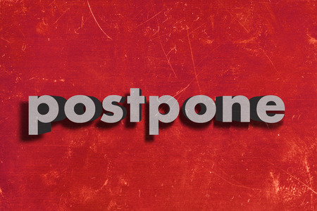 postpone: gray word on red wall