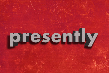 presently: gray word on red wall