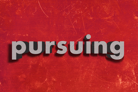 pursuing: gray word on red wall