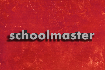 schoolmaster: gray word on red wall