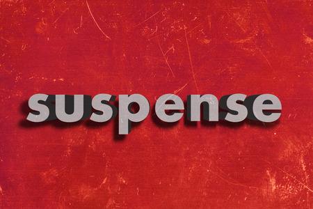 suspens: mot gris sur le mur rouge Banque d'images