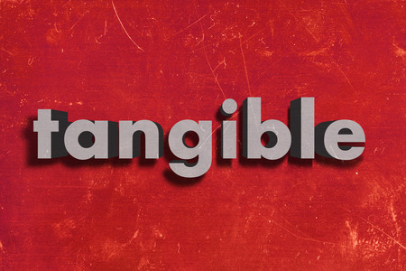 tangible: gray word on red wall