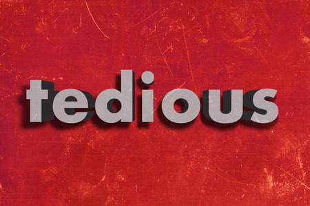 tedious: gray word on red wall