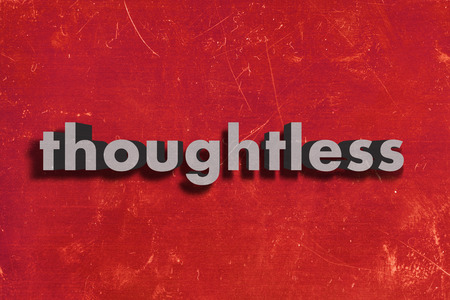 thoughtless: gray word on red wall