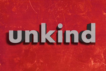 unkind: gray word on red wall