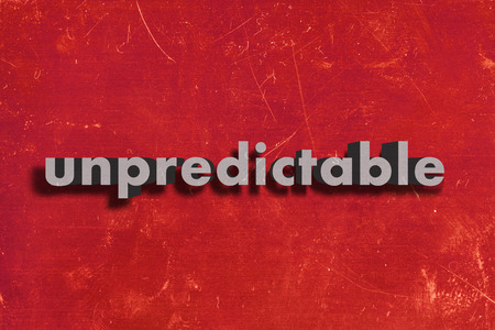 unpredictable: gray word on red wall