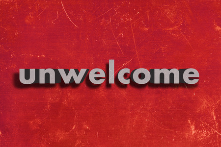 unwelcome: gray word on red wall