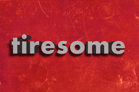 tiresome: gray word on red wall
