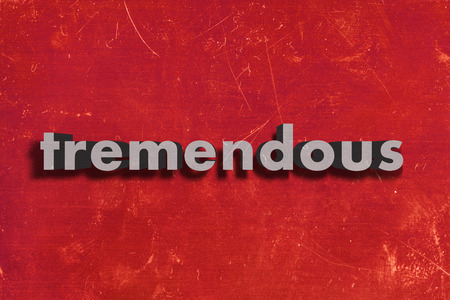 tremendous: gray word on red wall