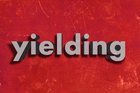 yielding: gray word on red wall