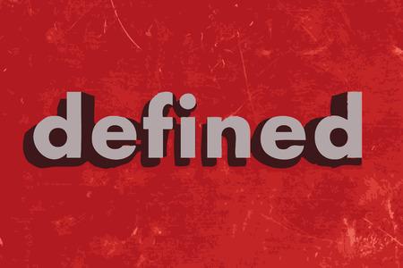 defined: definito parola vettore sul muro di cemento rosso