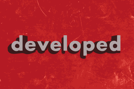 developed: developed vector word on red concrete wall