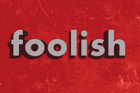 foolish: foolish word on red concrete wall