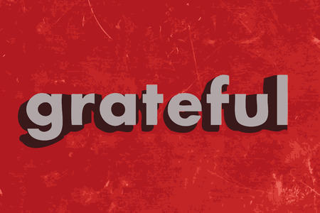 grateful: grateful word on red concrete wall