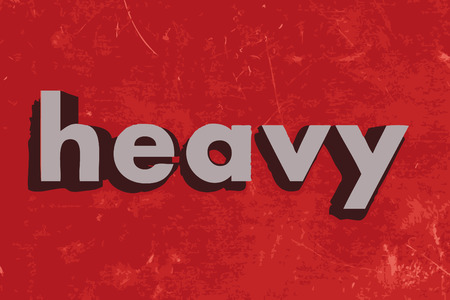 heavy: heavy word on red concrete wall