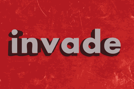invade: invade word on red concrete wall