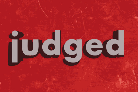 judged: judged word on red concrete wall