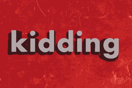 kidding: kidding word on red concrete wall