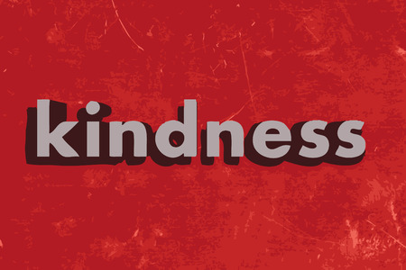 kindness: kindness word on red concrete wall